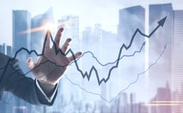 Businessman hand touching a graph hologram city. Hand of a businessman interacting with glowing growing graphs against a blurred city background. Concept of Royalty Free Stock Photos