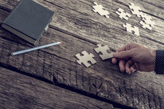 Hand of a businessman matching two puzzle pieces Royalty Free Stock Photo