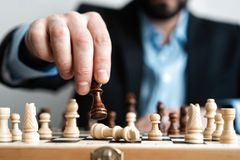 Hand of businessman moving chess figure in competition success play. strategy, management or leadership concept. Hand of businessman moving chess figure in stock photography