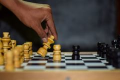 Hand of businessman moving chess figure in competition success play. Strategy, management or leadership concept on a wooden table stock photo