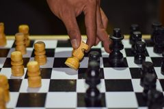 Hand of businessman moving chess figure in competition success play. Strategy, management or leadership concept on a wooden table stock images