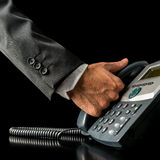 Hand of a businessman picking up the receiver. Close-up of the hand of a businessman picking up the receiver of a black land line telephone, placed on the desk Stock Image