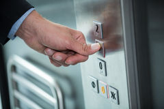 Hand of a businessman pressing the button in an elevator Royalty Free Stock Photography