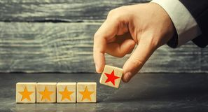 The hand of the businessman separates the fifth star from the other four. The loss of the fifth star, the fall in rating and recog royalty free stock photography