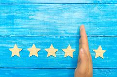 Hand of the businessman separates the fifth star from the other four. loss of the fifth star, the fall in rating and recognition. Critic takes the fifth star stock photos