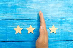 Hand of the businessman separates the third star from the other four. loss of the third star, the fall in rating and recognition. royalty free stock photo