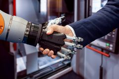 Hand of a businessman shaking hands with a Android robot stock image
