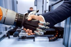 Hand of a businessman shaking hands with a Android robot royalty free stock photos