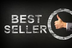 Hand of a businessman showing thumbs up for the phrase BEST SELLER written on a blackboard stock photo