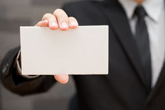 Hand of businessman showing white paper Stock Images