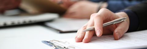Hand of businessman signing document with pen. Hand of businessman in suit filling and signing with silver pen partnership agreement form clipped to pad closeup Stock Images