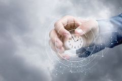Hand of a businessman in the sky shows the clock . royalty free stock photo