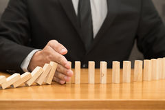 Hand of businessman stopping the domino effect. Risk control con Royalty Free Stock Photos