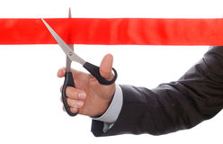 Hand of businessman in suit cutting red ribbon with pair of scis Royalty Free Stock Photography