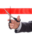 Hand of businessman in suit cutting red ribbon with pair of scis Royalty Free Stock Image