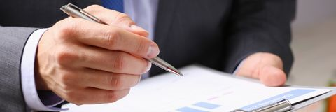 Male hand holding silver pen. Hand of businessman in suit filling and signing with silver pen partnership agreement form clipped to pad closeup. Management Royalty Free Stock Images