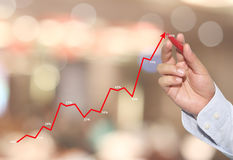 hand of Businessman touch line graph business in peak point. Stock Photos