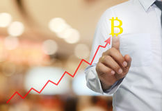 Hand of businessman touche to symbol of bitcoin in business grap. H concept of electronic money network in present your work Stock Photo