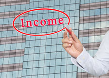 Hand of businessman using red pen pointing to text of Income on. Glass window of tall building background,concept of investment and benefit Stock Photo