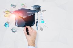 Man hand drawing education sketch. Hand of businessman wearing white shirt drawing colorful education sketch and graduation hat on white wall with geometric royalty free stock photos