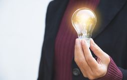 Hand of businesswoman holding light bulb for idea or success or. Hand of businesswomean holding light bulb for idea or success or solar energy Royalty Free Stock Image