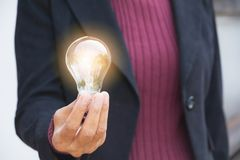 Hand of businesswoman holding light bulb for idea or success or. Hand of businesswomean holding light bulb for idea or success or solar energy Stock Images