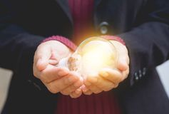 Hand of businesswoman holding light bulb for idea or success or. Hand of businesswomean holding light bulb for idea or success or solar energy Stock Photography