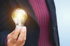 Hand of businesswoman holding light bulb for idea or success or. Hand of businesswomean holding light bulb for idea or success or solar energy Royalty Free Stock Photo