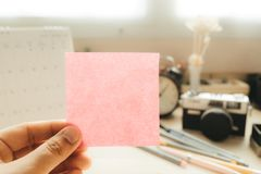 Hand of businesswoman holding post it note with camera and calendar placed background. image for workplace, note, blank concept. Hand of businesswoman holding Royalty Free Stock Image