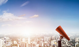 Hand of businesswoman holding red paper trumpet against cityscape background Royalty Free Stock Photo