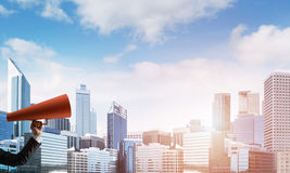 Hand of businesswoman holding red paper trumpet against cityscape background Royalty Free Stock Photography