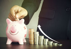 hand of businesswoman put money on pink of piggy bank Royalty Free Stock Photos