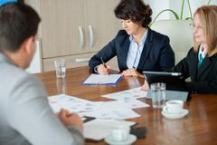 Hand of businesswoman signing a contract in the meetinf room royalty free stock images