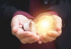 Hand of businesswoman holding light bulb for idea or success or. Hand of businesswomean holding light bulb for idea or success or solar energy Stock Photos