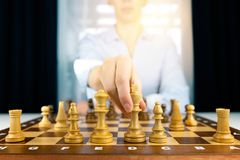 Hand of businesswomen moving chess figure in competition success play. strategy, management or leadership concept royalty free stock image
