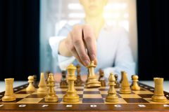 Hand of businesswomen moving chess figure in competition success play. strategy, management or leadership concept stock photos