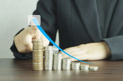 Hand of businesswomen  points arrow on  pile of coins. On blue background, concept in growth, save and investment in business Royalty Free Stock Photos