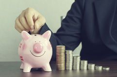 hand of businesswomen put money on pink of piggy bank Stock Image