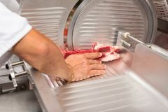 Hand of butcher using slicer in butcher shop Stock Photography