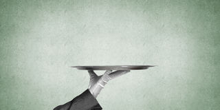 Hand of butler holding empty metal tray against concrete background. Waiter hand in white glove presenting empty tray Stock Photos