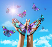 Hand and butterfly hand painting, tattoo, over a blue sky. Royalty Free Stock Photo