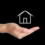 Hand with Cabin. Hand underneath illustration of white cabin with black studio background stock images