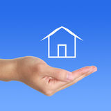Hand with Cabin. Hand underneath illustration of white cabin with blue background royalty free stock photos