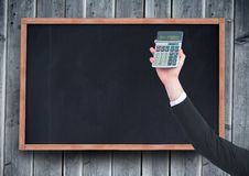 Hand with calculator against chalkboard and grey wood panel. Digital composite of Hand with calculator against chalkboard and grey wood panel royalty free stock photography