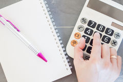 Hand with calculator and notepad Stock Photography