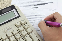 Hand on calculator paper and pen Stock Image