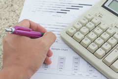 Hand on calculator paper and pen Stock Photography