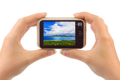 Hand with camera and beach landscape (my photo) Royalty Free Stock Images