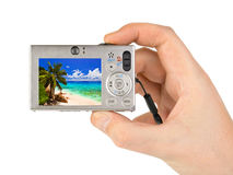 Hand with camera and beach landscape (my photo) Stock Images