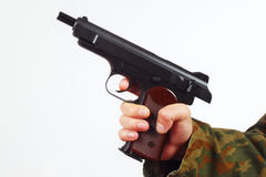 Hand in camouflage uniform with discharged gun on white background Royalty Free Stock Images